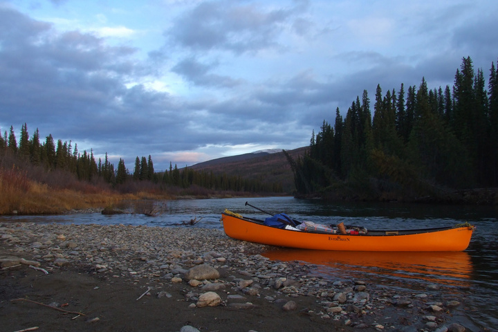 Canoe on the river, with a dusting of snow in the background