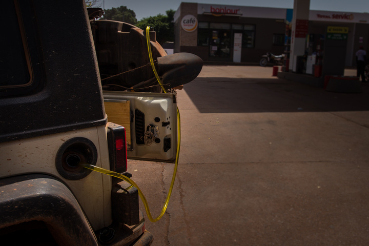 Gas was cheaper in Ivory Coast, so I'm transferring Ivorian gas into my tank from the Titan tank while at a gas station in Mali :)